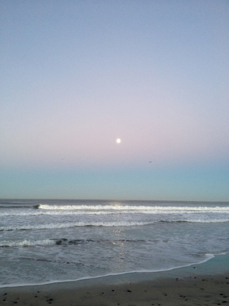 The full moon sets and the sun rises at Carlsbad Beach, San Diego County, California
